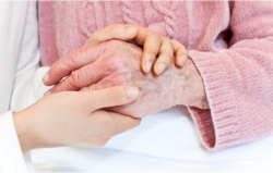 Caregiver holding the hand of old woman